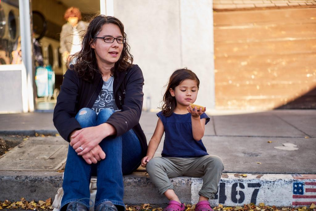 Jen and her daughter enjoying a snack sitting on the curb.